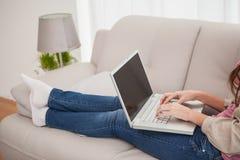 Vrij donkerbruin gebruikend laptop op de laag Royalty-vrije Stock Afbeeldingen