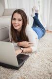 Vrij donkerbruin gebruikend laptop op de vloer Stock Foto