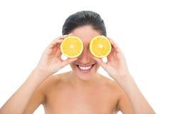 Vrij donkerbruine holding twee de oranje helften over haar ogen Royalty-vrije Stock Fotografie