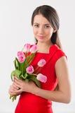 Donkerbruine vrouw die roze bloemen houden stock foto
