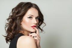 Vrij donkerbruine modelvrouw met make-up en bruin krullend portret stock afbeeldingen