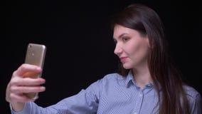 Vrij donkerbruine onderneemster die in blauwe blouse selfie-foto's maken die smartphone gebruiken die ernstig bij zwarte achtergr stock footage