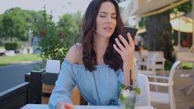 Vrij donkerbruine vrouwenzitting in openluchtrestaurant en het gebruiken van haar mobiele telefoon stock videobeelden