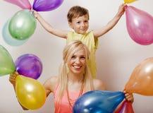 Vrij echte familie met kleurenballons op witte achtergrond, blonde vrouw met weinig jongen bij verjaardagspartij het heldere glim Stock Afbeelding