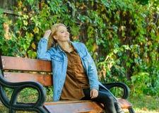 Vrij en ontspannen het voelen Het vrouwenblonde neemt onderbreking het ontspannen in park U verdient onderbreking voor ontspant M royalty-vrije stock foto
