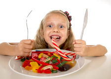 Vrij gelukkig Kaukasisch vrouwelijk kind die schotelhoogtepunt van suikergoed in het zoete gevaarlijke dieet van het suikermisbru Royalty-vrije Stock Afbeeldingen