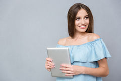 Vrij gelukkige jonge vrouwelijke holding tablet en het glimlachen Stock Foto's