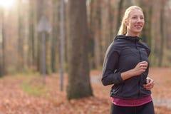 Vrij geschikte jonge vrouwenjogging in bos Royalty-vrije Stock Foto