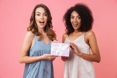 Vrij geschokte jonge twee vrouwen die gift huidige doos houden royalty-vrije stock afbeelding
