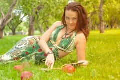 Vrij glimlachend gelukkig meisje in het groene boek van de kledingslezing en het liggen op het gras stock foto