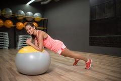 Vrij, glimlachend meisje met een geschiktheidsbal Wijfje die op een vage gymnastiekachtergrond uitoefenen Aerobicsconcept De ruim stock afbeeldingen
