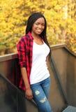 Vrij glimlachende Afrikaanse vrouw die rood geruit overhemd in de zonnige herfst dragen Royalty-vrije Stock Fotografie