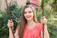 Vrij het gelukkige donkerbruine slingeren die dichtbij huis in park op een zonnige dag glimlachen royalty-vrije stock afbeeldingen