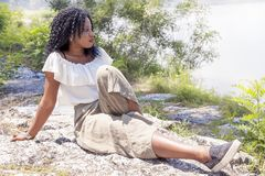 Vrij het ivorian meisje stellen op de bank van een rivier stock foto