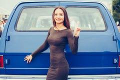 Vrij het jonge meisje stellen dichtbij blauw SUV in sexy kleding en toont overwinningsteken Sexy kuiken Royalty-vrije Stock Foto's