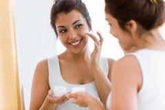 Vrij het jonge vrouw geven van haar huid die zich dichtbij spiegel in de badkamers bevinden Stock Foto's