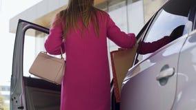 Vrij het vrouwelijke lopen aan auto na het winkelen, vrouw die in auto krijgen stock video