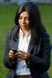 Vrij Indisch meisje dat mobiele telefoon met behulp van Stock Afbeelding