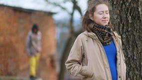 Vrij jeugdig bruin-haired zwanger meisje in de beige gezichten van de laagvergadering met lange vreemdeling in kap en gele broeke stock videobeelden
