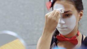 Vrij jong boots het toepassen van witte verf op haar gezicht voor kleine spiegel na stock footage