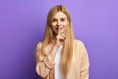 Vrij jong gelukkig blondemeisje die stiltegebaar over blauwe achtergrond tonen stock foto