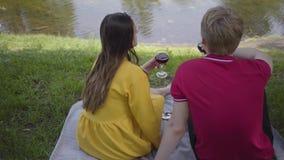 Vrij jong gelukkig paar in liefde die picknick met wijn in mooie bloeiende tuin of park maken die cheerfully babbelen en stock footage