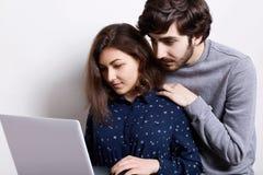 Vrij jong meisje die donker overhemd dragen die iets op laptop PC tonen aan haar vriend Een modieuze hipster met baard die op van royalty-vrije stock foto