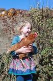 Vrij jong meisje die een bruine kip houden Stock Foto's