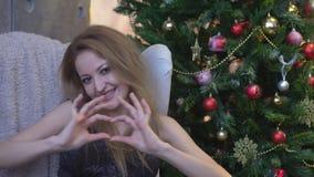 Vrij jong meisje die een hart met haar handen op de achtergrond van de Kerstmisboom maken stock footage