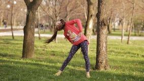 vrij jong meisje die oefeningen op het gras in het de lentepark doen stock video
