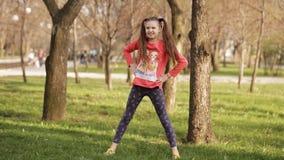 vrij jong meisje die oefeningen op het gras in het de lentepark doen stock videobeelden