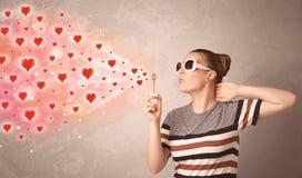 Vrij jong meisje die rode hartsymbolen blazen Royalty-vrije Stock Afbeelding