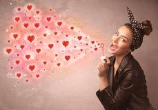 Vrij jong meisje die rode hartsymbolen blazen Stock Afbeeldingen