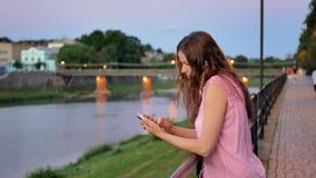 Vrij jong meisje die smartphone met oortelefoons gebruiken dichtbij het traliewerk op waterkant in avondtijd, oude stad, rivier e stock videobeelden