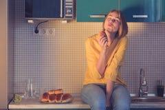 Vrij jong meisje met een glimlach op haar gezicht die gebakje eten laat bij nachtzitting op de lijst in de keuken royalty-vrije stock fotografie