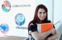 Vrij jong meisje met lange mooie haarstudie op universiteit, Stock Foto
