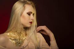 Vrij jong model met lang blondehaar en gouden folie op haar Royalty-vrije Stock Foto's