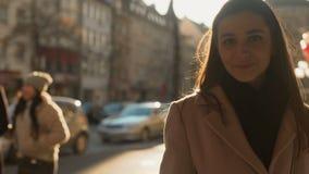 Vrij jong wijfje die charmingly aan camera glimlachen die, achtergrond zich in openlucht bevinden stock footage
