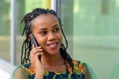 Vrij in jonge Afrikaanse vrouw op mobiel haar stock foto