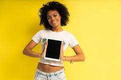 Vrij jonge afro Amerikaanse vrouw die die en tabletcomputer bevinden met behulp van over gele achtergrond wordt geïsoleerd royalty-vrije stock foto's