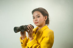 Vrij jonge Aziatische onderneemster die in geel kostuum verrekijkers houden. Stock Fotografie