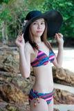 Vrij Jonge Aziatische vrouw in bikini het ontspannen op het strand royalty-vrije stock fotografie