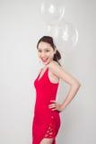 Vrij jonge Aziatische vrouw die rode kleding met in hand ballons dragen Royalty-vrije Stock Foto