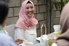 Vrij jonge Aziatische vrouwen die terwijl het hebben van lunch met vrienden glimlachen stock foto's