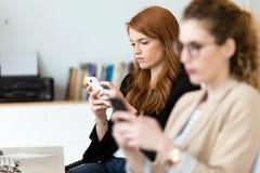 Vrij jonge bedrijfsvrouw die haar mobiele telefoon in het bureau met behulp van stock foto