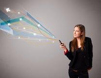 Vrij jonge dame die een telefoon met kleurrijke abstracte lijnen a houden Stock Afbeelding