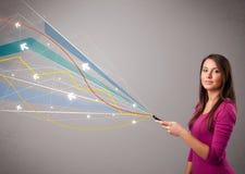 Vrij jonge dame die een telefoon met kleurrijke abstracte lijnen a houden Royalty-vrije Stock Foto