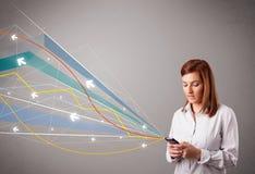 Vrij jonge dame die een telefoon met kleurrijke abstracte lijnen a houden Stock Afbeeldingen