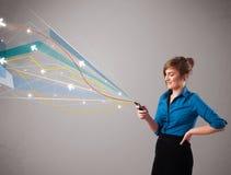 Vrij jonge dame die een telefoon met kleurrijke abstracte lijnen a houden Royalty-vrije Stock Afbeeldingen