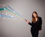 Vrij jonge dame die een telefoon met kleurrijke abstracte lijnen a houden Royalty-vrije Stock Fotografie